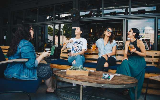 Photo of four people laughing in a cafe